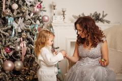 Mother and daughter decorate a Christmas tree. Stock Photos