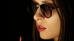 Girl Paints Her Lips With Red Lipstick on Black Background Stock Footage