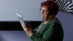 Lonely grandmother using tablet computer, she looking pictures Stock Footage