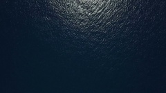 Aerial - Top down view of a deep blue sea rippling water surface Stock Footage
