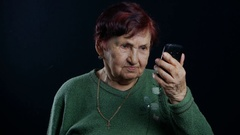 Old woman talking on mobile phone at black background Arkistovideo
