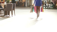 Pretty woman walking in big mall after shopping. She is wearing blue short dress Stock Footage