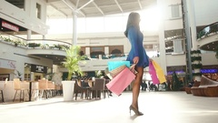 Girl revolves around after shopping. She is wearing blue short dress and black Stock Footage