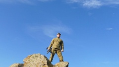 Soldier  lift up hand and   automatic rifle  against blue sky. Slow Motion Stock Footage