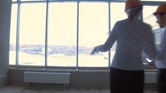 Businessman and business woman in suit, hard hat in a new unfinished office Stock Footage