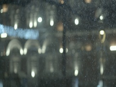 Snow is falling in the evening with background building with spectacular lights Stock Footage