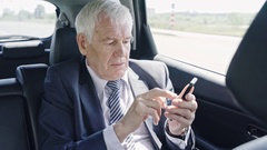 Senior Businessman with Mobile Phone in Car Stock Footage