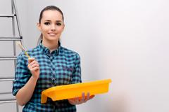Woman painting house in DIY concept Stock Photos