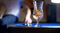 View of alcoholic drink and man in the background collecting billiard's balls Stock Footage