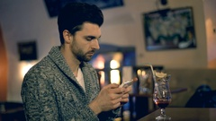 Handsome man in warm jumper sitting in the pub and texting on smartphone Stock Footage