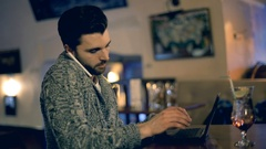 Man talking on cellphone while typing something on laptop in the restaurant Stock Footage