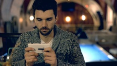 Handsome man sitting next to the billiard's table and using smartphone Stock Footage
