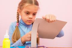 The child cuts a strip of cardboard in the classroom Stock Photos