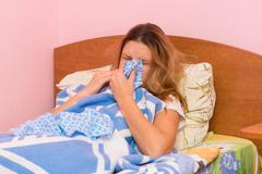 She sneezes ill with acute respiratory illness Stock Photos