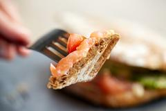 Person eating salmon panini sandwich at restaurant Stock Photos