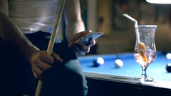 Man holding cue while sitting on billiard's table and using smartphone Stock Footage