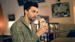 Handsome man drinking alcoholic beverage in a pub and looking thoughtful Stock Footage
