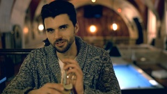 Handsome man talking with someone and drinking alcoholic beverage Stock Footage