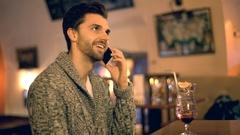 Handsome man chatting on cellphone and drinking alcoholic beverage Stock Footage