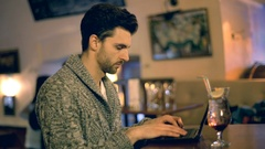 Man looking absorbed while sitting in a pub and typing something on laptop Stock Footage