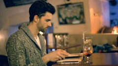 Absorbed man looking for something in a book while sitting in a pub Stock Footage