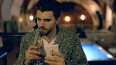Happy man reading something on smartphone and drinking alcoholic beverage Stock Footage