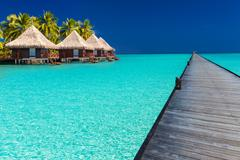 Wodden jetty extended into azure water of lagoon with villas over the water Stock Photos