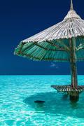 Bamboo beach umbrella in the water of tropical island Stock Photos