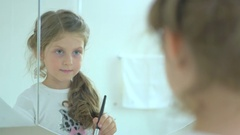 The little girl powder the face in the mirror Stock Footage