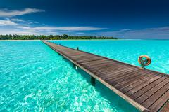 Long wooden jetty over atoll and a tropical island in Maldives Stock Photos