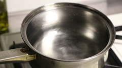 A person places a pot of water on a burner gas stove to boil water. Stock Footage