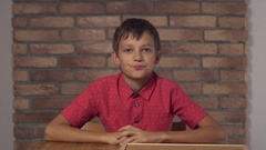 Child sitting at the desk holding flipchart with lettering taxi on the Stock Footage
