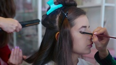 Make up artist applying eyeshadow while hairstylist making hair-do. Stock Footage