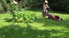 Peasant girl in dress and flip-flop mow lawn with grass cutter in yard. 4K Stock Footage