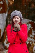 Young woman shivering with cold on a forest wearing a red overcoat Stock Photos
