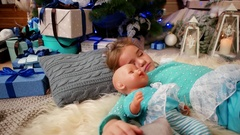 Little cute girl sleep, near the fireplace where the fire burns, hugging a doll Stock Footage