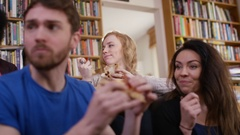 4K Large group of happy young friends eating takeaway pizza at home Arkistovideo