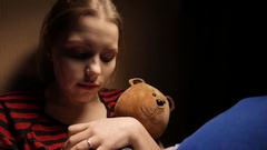 Teenage writing diary at home in her bad with a toy bear and little doggy. 4K Stock Footage