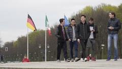 Teenagers walk in Berlin, German, Mexican, EU flags in background, Germany Stock Footage