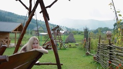 Young woman take a rest on the big woode swing Stock Footage