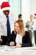 Co-workers discussing business document on xmas eve Stock Photos
