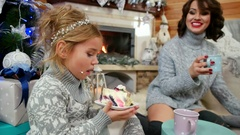 Girl eating a large piece of cake at The Christmas tree, mom and daughter Stock Footage