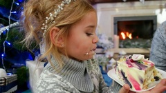 Girl with pleasure eating a large piece of cake at The Christmas tree, Family by Stock Footage