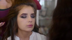 Make up artist applying powder while hairdresser making hair-do slow motion Stock Footage