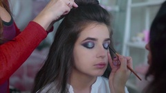 Make up artist applying glitter eyeshadows while hairdresser making hair-do Stock Footage