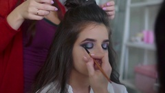 Make up artist applying eyeshadows while hairdresser making hair-do Stock Footage