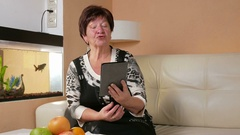 Senior woman talking on the tablet PC with a girlfriend. She sits on the couch Stock Footage