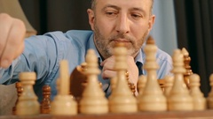 Man moving a chess piece on wooden chessboard Stock Footage
