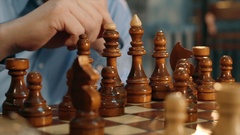 Hand moving a knight chess piece on wooden chessboard Stock Footage