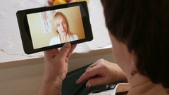 Senior woman coughing and communicate with a doctor on a video conference Stock Footage